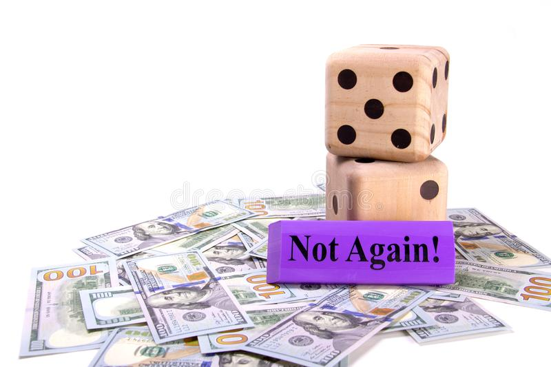 Large wooden dice sitting on top of scattered US dollars. Concept gambling on your future savings and investments. stock image
