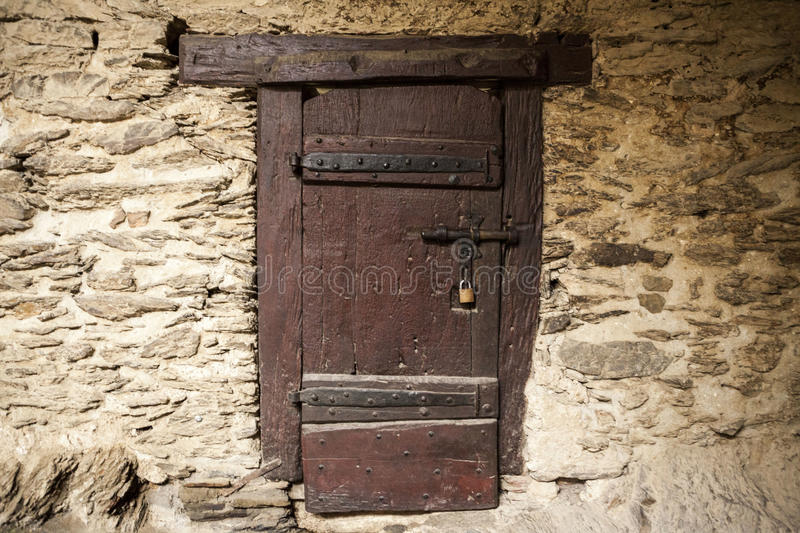 A Large Wooden Door Closed An Old Fortress In The Stone Wall Of The ...