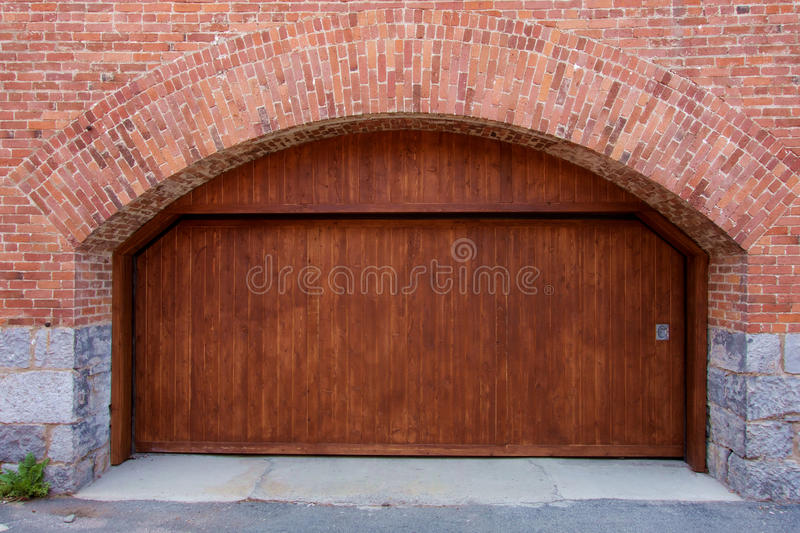 A Large Modern Wooden Garage Door With Stone And Brick Arch.