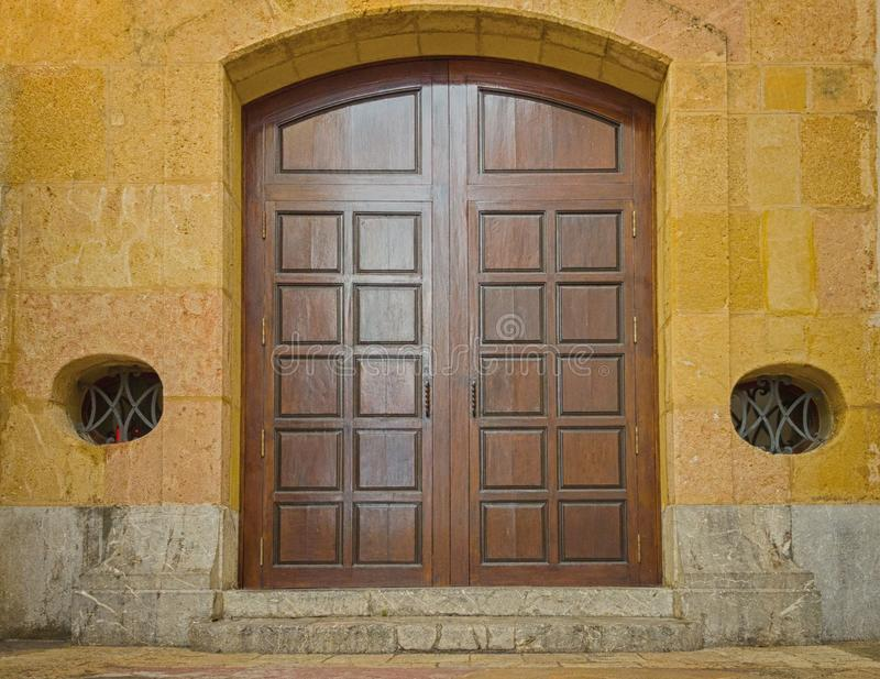The large wooden gate of the old stone Church stock photo