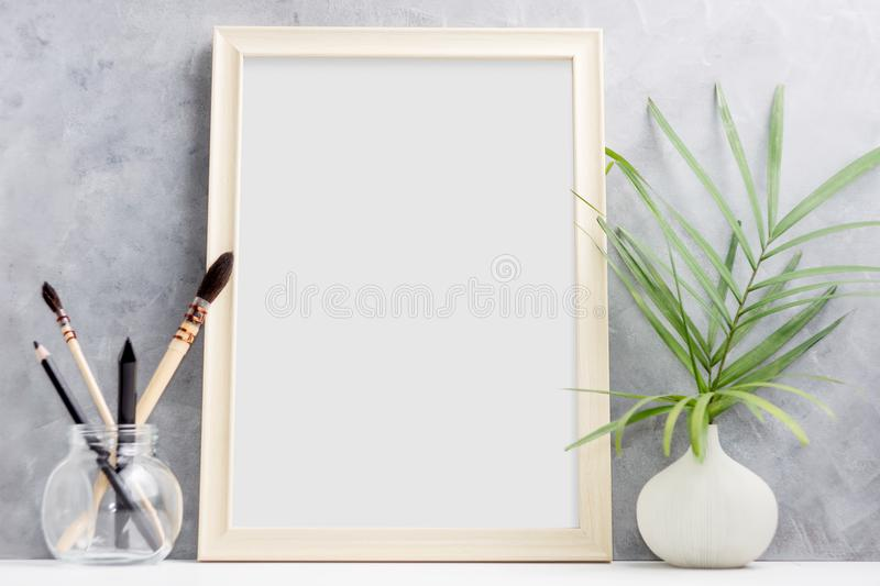 Large wooden Photo frame mock up with green palm leaves in vase and brushes in glass on shelf. Scandinavian style stock photos