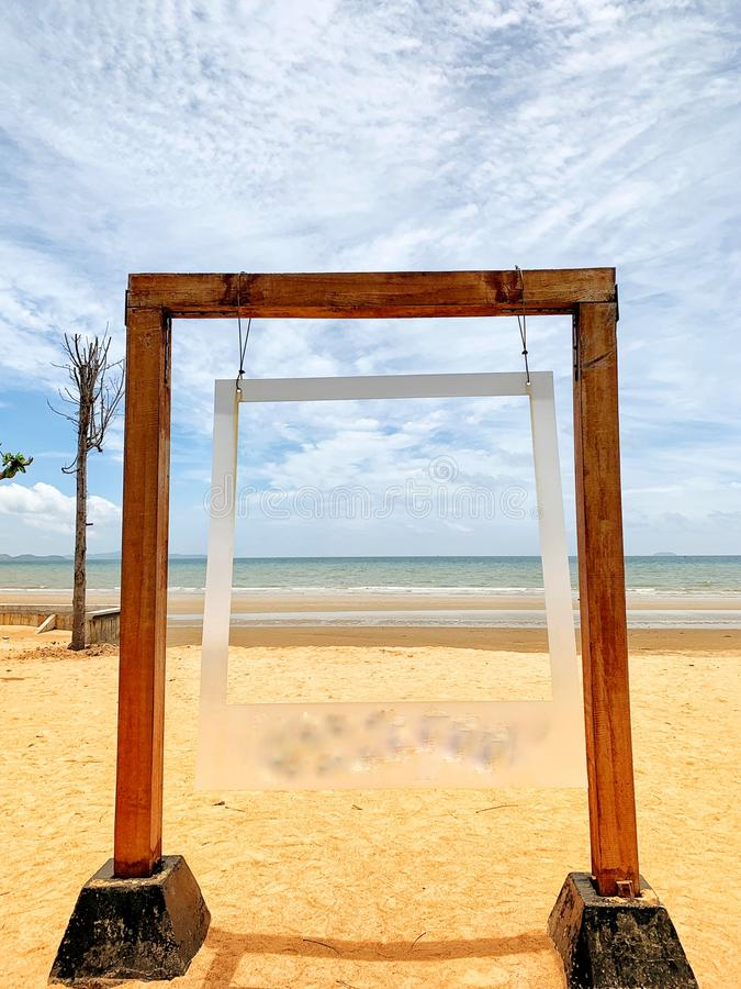 Large wooden picture frame on a sandy beach background, background, landscape, sea and beautiful sky.  Holiday Concept stock images