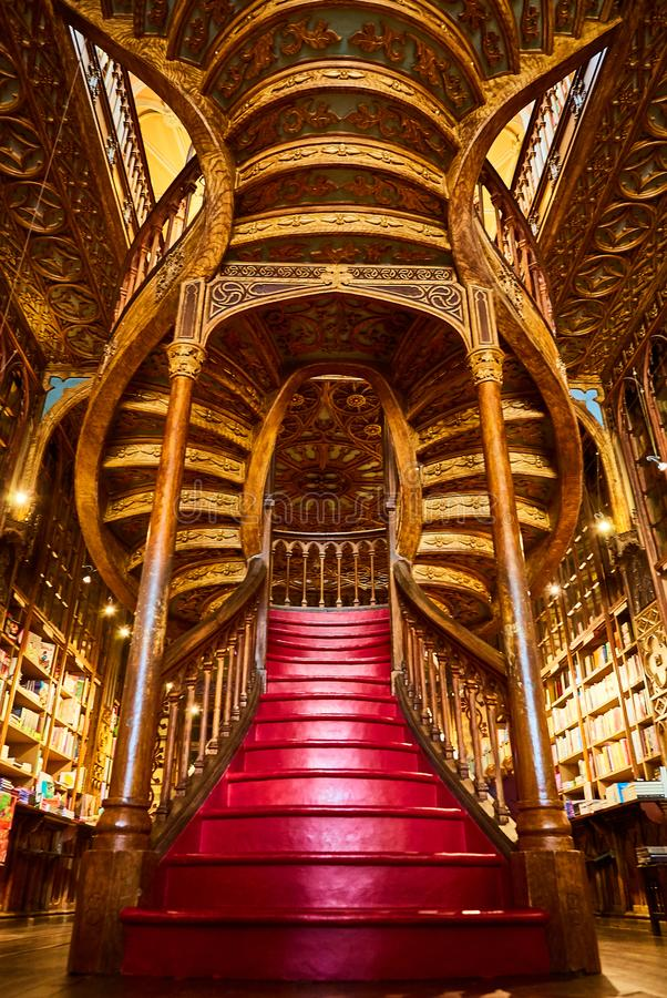 Large wooden staircase with red steps inside library bookstore Livraria Lello in historic center of Porto, famous for Harry Potter. Large wooden staircase with stock photos