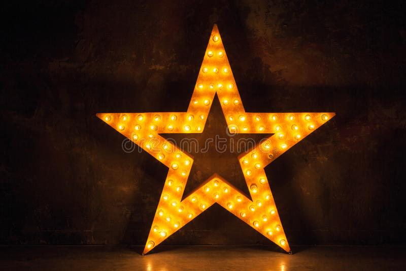 Large wooden star with a large amount of lights in front of dark concrete background. Large wooden star with a large amount of lights in front of the dark stock images