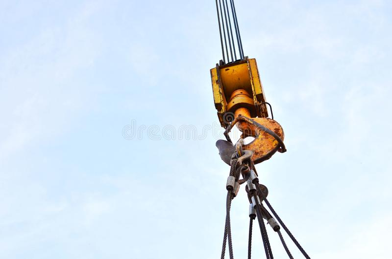 Large yellow crane hook on lifting fears and chains hanging on it for lifting loads on a background of blue sky. Construction concept - Image royalty free stock photo