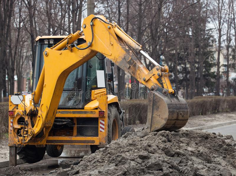 A large yellow excavator stands in the middle of the street near the dug hole stock image