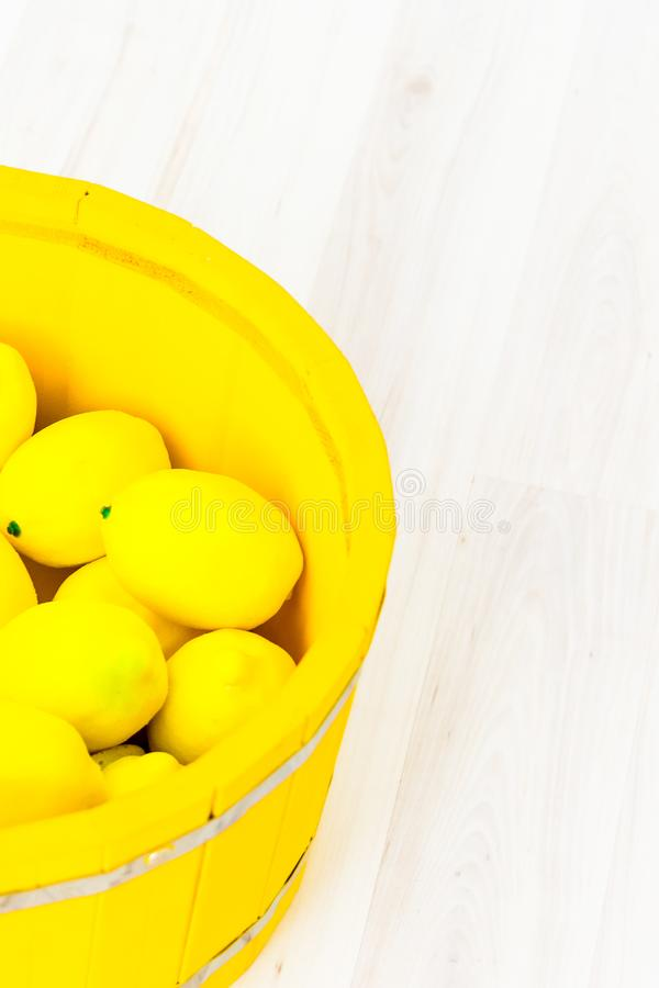 Large yellow lemons in a large wooden basin standing on the floor. Large yellow lemons in a large yellow wooden basin standing on the floor stock photography