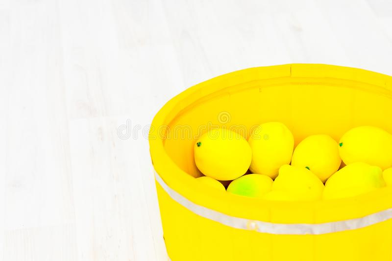 Large yellow lemons in a large wooden basin standing on the floor. Large yellow lemons in a large yellow wooden basin standing on the floor royalty free stock images
