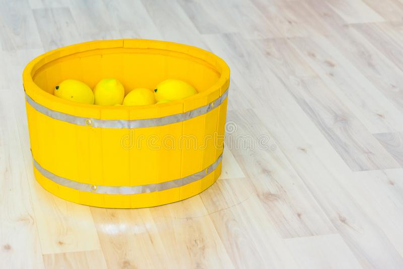 Large yellow lemons in a large wooden basin standing on the floor. Large yellow lemons in a large yellow wooden basin standing on the floor royalty free stock photo
