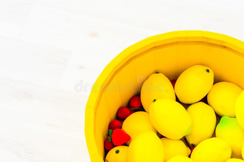 Large yellow lemons in a large wooden basin standing on the floor. Large yellow lemons in a large yellow wooden basin standing on the floor stock photos