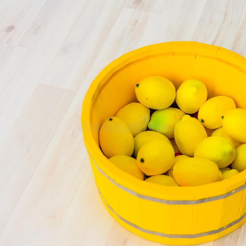 Large yellow lemons in a large wooden basin standing on the floor. Large yellow lemons in a large yellow wooden basin standing on the floor stock images