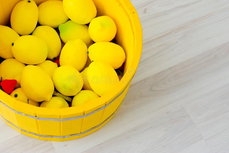 Large yellow lemons in a large wooden basin standing on the floor. Large yellow lemons in a large yellow wooden basin standing on the floor royalty free stock image