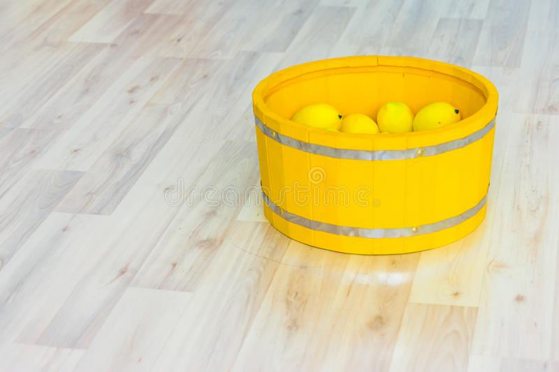 Large yellow lemons in a large wooden basin standing on the floor. Large yellow lemons in a large yellow wooden basin standing on the floor royalty free stock photos