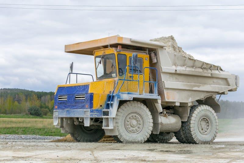 Large-yellow quarry dump trucks produce transportation of minerals royalty free stock photo