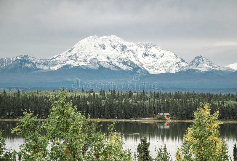The largest National Park in America, Wrangell St Elias. Towers above a small lake cabin royalty free stock image