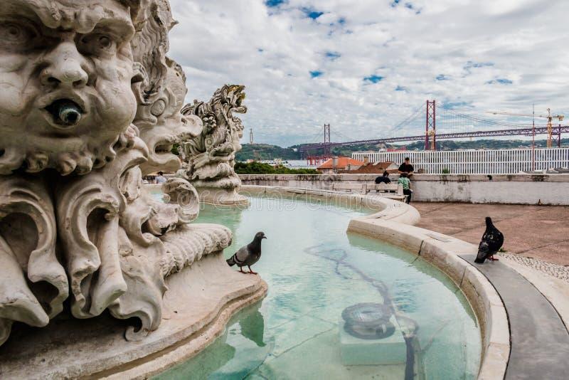 Largo das Necessidades, Lissabon, Portugal - sikt av Cristo Rei och 25 de Abril Bridge längs springbrunnen och de dekorativa skul royaltyfri fotografi