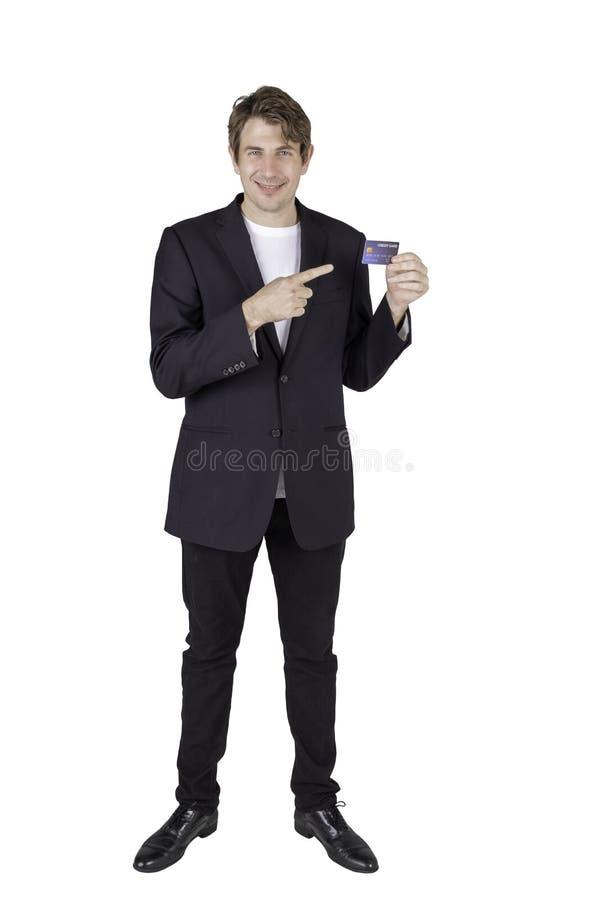 Largo retrato de un hombre de negocios apuesto que sostiene una tarjeta de crédito y mira directamente a la cámara fotografía de archivo