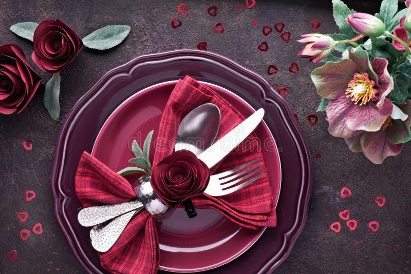 Largura plana com pratos de burgindes e crockery decorada com rosas e anêmonas, preparação de jantar de Natal ou de Valentine fotos de stock royalty free