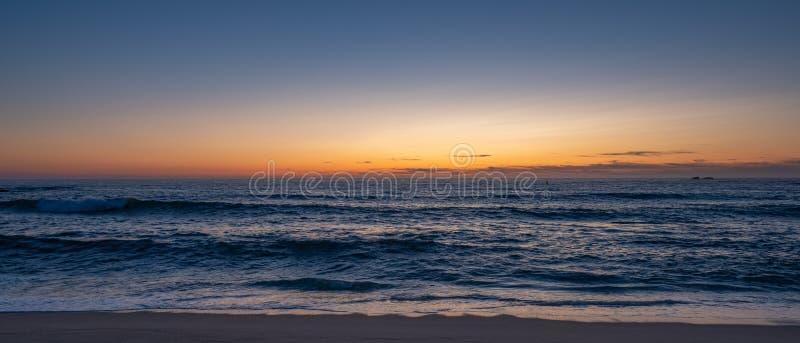 Largura sobre a praia ao anoitecer, paralela à costa com o céu azul-laranja gradiente fotografia de stock royalty free