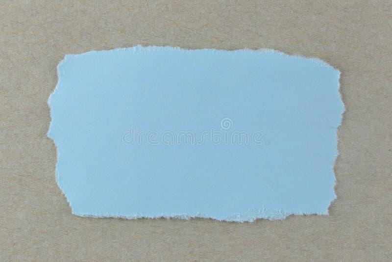 Larme de papier bleu sur le fond brun de carton images libres de droits