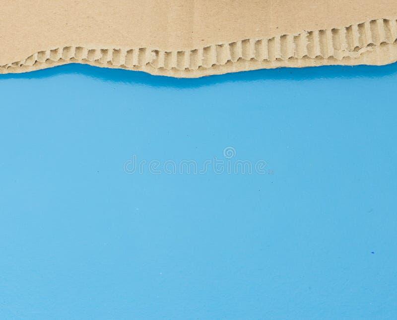 Larme de papier de Brown contre le bleu photos stock