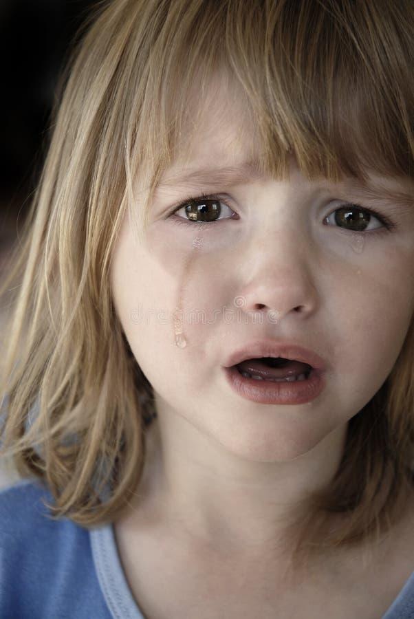 Larmes pleurantes de petite fille fonctionnant en bas des joues images libres de droits