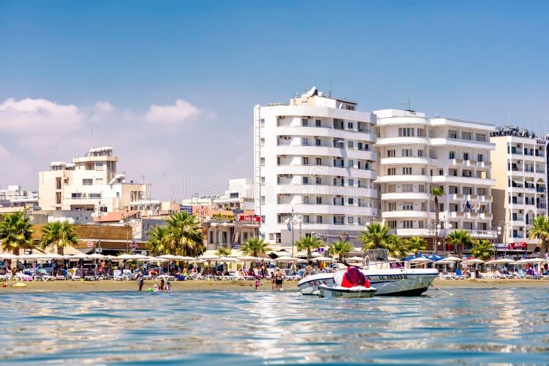 LARNACA, CYPRUS - AUGUSTUS 27, 2016: Finikoudesstrand met de talrijke hotels en de koffie op de achtergrond stock afbeeldingen