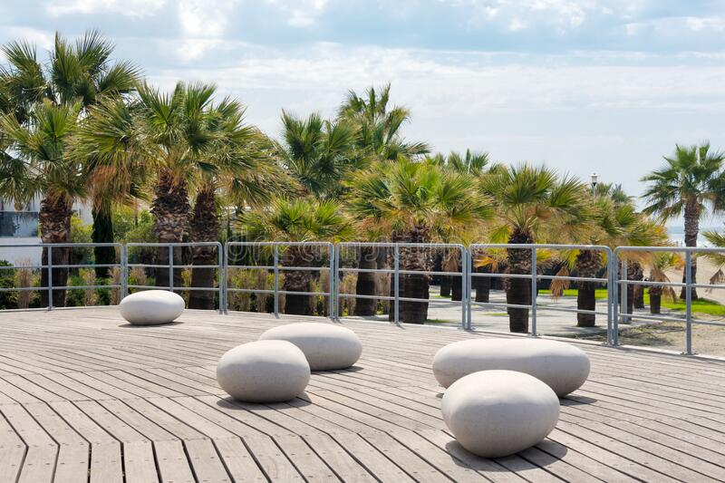 Larnaca embankment, Cyprus in spring. View of Larnaca seafront with palm trees and stone shaped benches, park zone near the beach royalty free stock photos