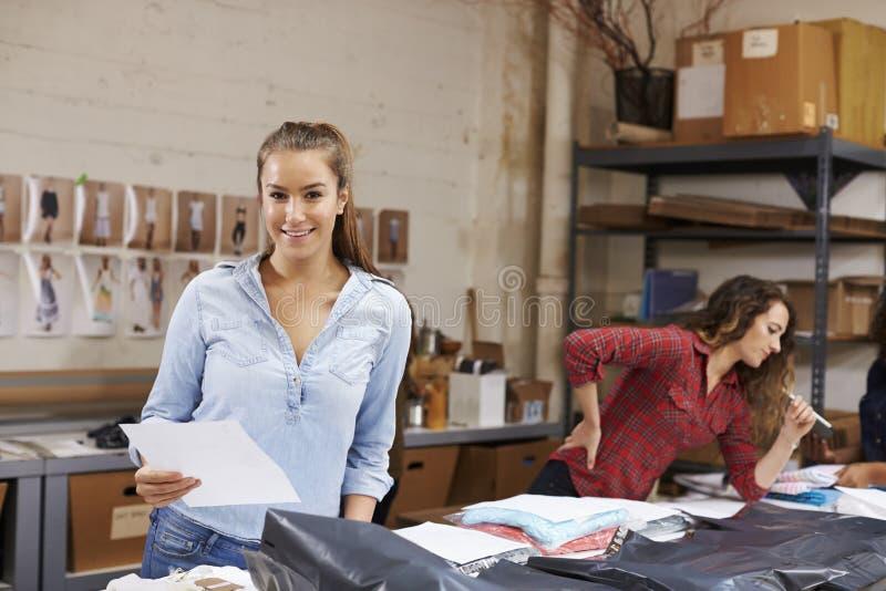 Las órdenes del embalaje de la mujer joven para la distribución sonríen a la cámara fotografía de archivo libre de regalías