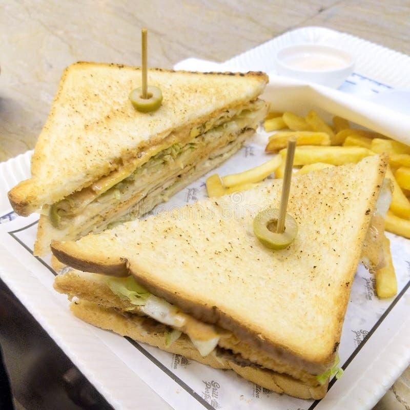 Las aceitunas asadas a la parrilla del pollo del club intercalan con las patatas fritas imágenes de archivo libres de regalías