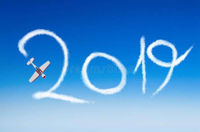Las acrobacias aéreas ligeras de los aviones del motor dibujan en el cuadro 2019 Feliz Año Nuevo del cielo imagen de archivo libre de regalías