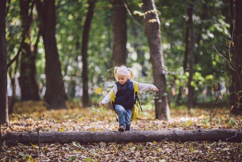 Las actividades al aire libre de los niños del tema El pequeño bebé divertido que la muchacha rubia caucásica camina a través del imagen de archivo libre de regalías