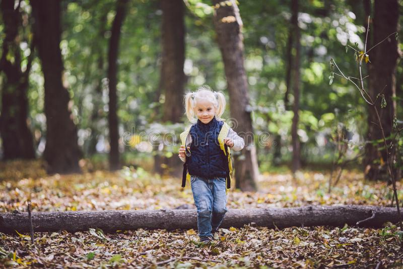 Las actividades al aire libre de los niños del tema El pequeño bebé divertido que la muchacha rubia caucásica camina a través del foto de archivo libre de regalías
