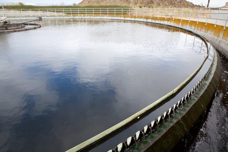 Las aguas residuales fluyen sobre los vertederos en una depuradora de aguas residuales  imagen de archivo libre de regalías