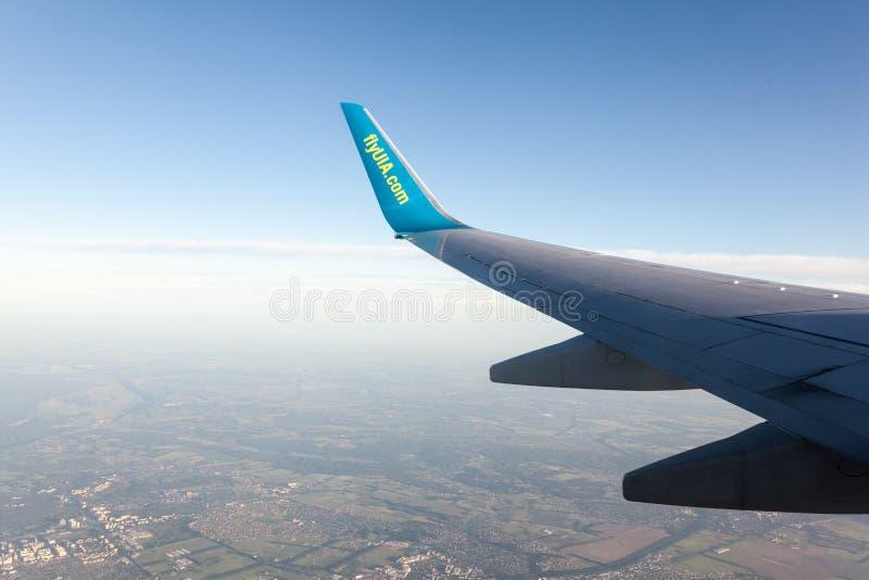 Las alas de las líneas aéreas internacionales ucranianas del aeroplano están sobre el cielo claro en la puesta del sol imágenes de archivo libres de regalías