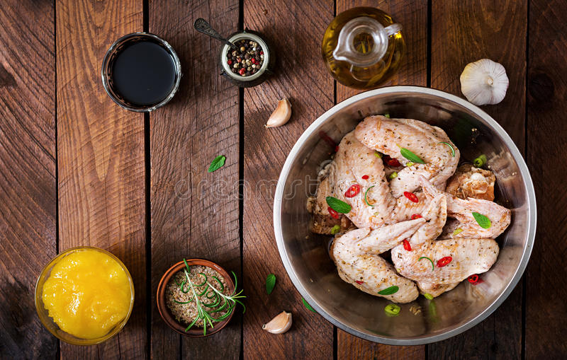 Las alas de pollo adobadas crudas se prepararon en estilo asiático con la miel, el ajo, la salsa de soja y las hierbas foto de archivo
