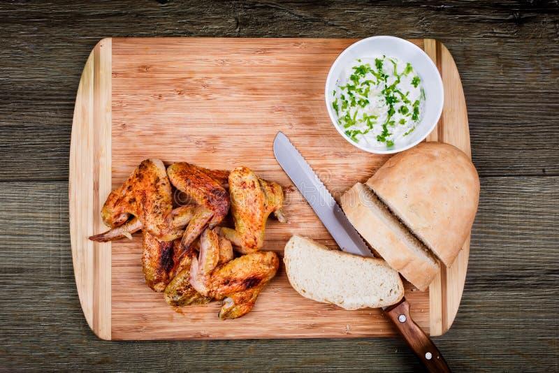 Las alas de pollo asadas a la parrilla deliciosas con la salsa, el cuchillo y el pan de ajo en una tabla de cortar en fondo rústi fotos de archivo libres de regalías