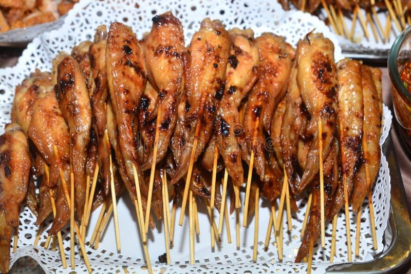 Las alas de pollo asadas a la parrilla ensartan la madera imagenes de archivo