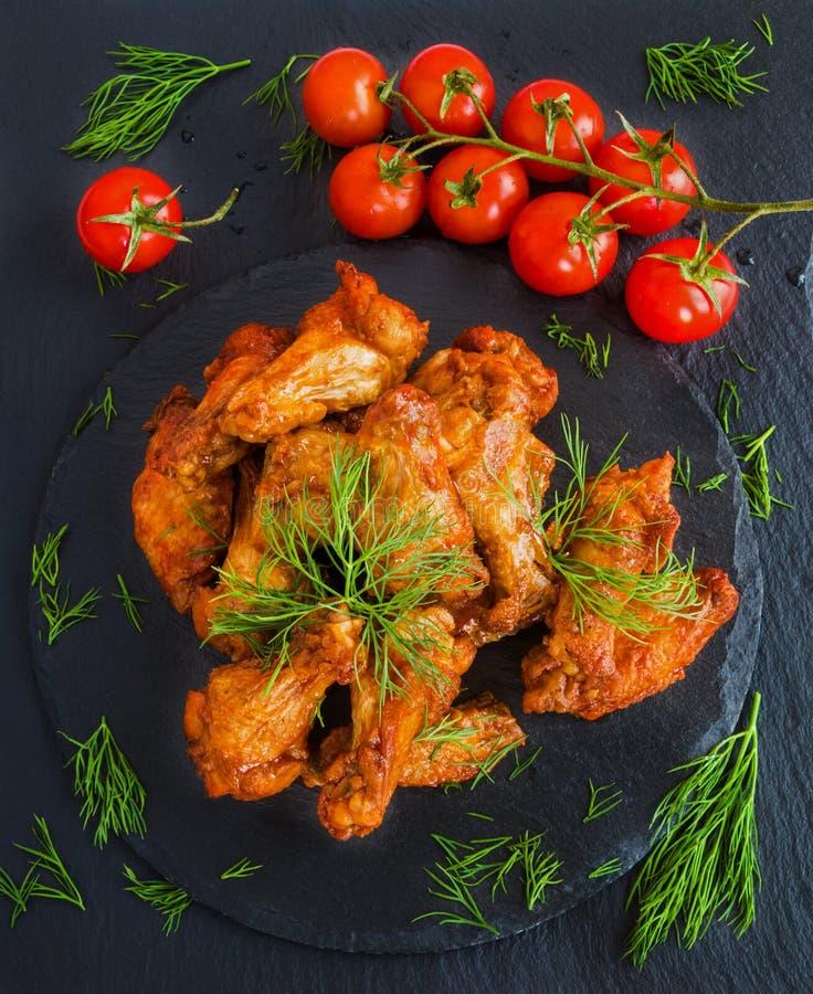 Las alas de pollo cocinaron con la salsa de barbacoa en fondo de piedra negro Pequeños tomates y eneldo de cereza Visión superior imagenes de archivo
