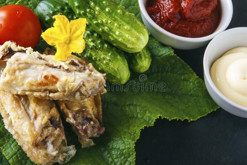 Las alas de pollo deliciosas sanas en un pepino verde se van con las verduras orgánicas frescas en un fondo negro Foo rústico die fotos de archivo
