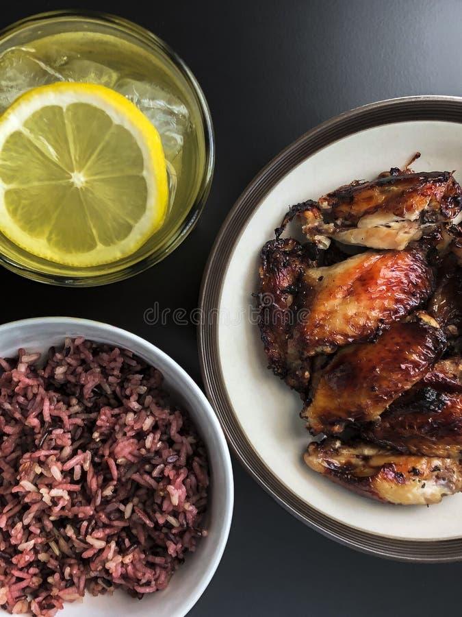 Las alas de pollo frito del aire en plato de cerámica sirven con el pequeño cuenco de Riceberry cocinado y un vidrio de té verde  fotos de archivo libres de regalías