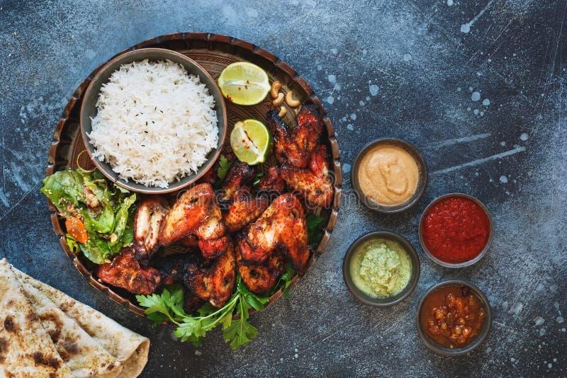Las alas de pollo de Tandoori sirvieron con diversas salsas de inmersión de la salsa picante fotografía de archivo libre de regalías