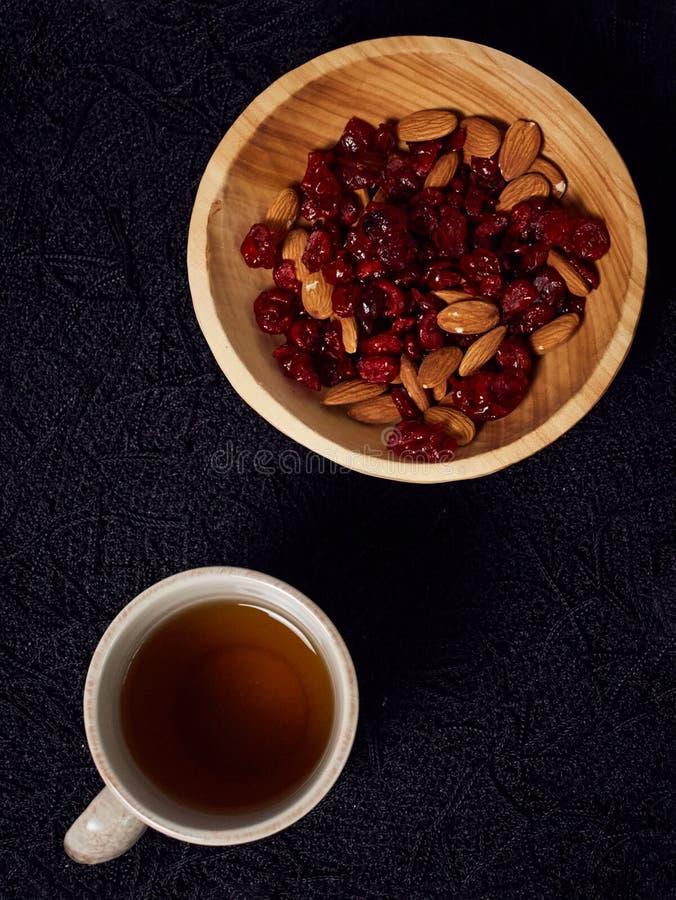 Las almendras de un cuenco y las bayas de madera del goji se mezclaron, al lado de una taza llenada de té, en una manta negra del imagen de archivo libre de regalías