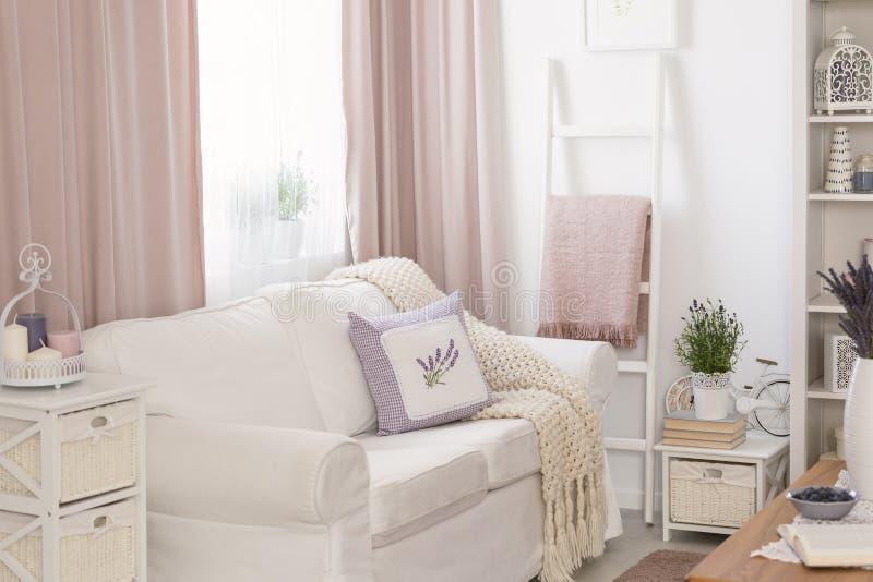 Las almohadas y la manta en el sofá blanco en interior rosado de la sala de estar con cubre y florece Foto verdadera fotos de archivo libres de regalías
