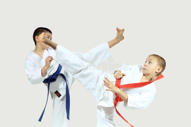Las altas piernas de los soplos son sportsmens del golpe en karategi imagen de archivo
