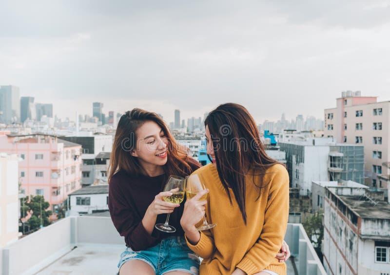 Las amigas felices de Asia gozan de risa y de la copa de vino chispeante alegre en el partido del tejado, celebración festiva, te imagenes de archivo
