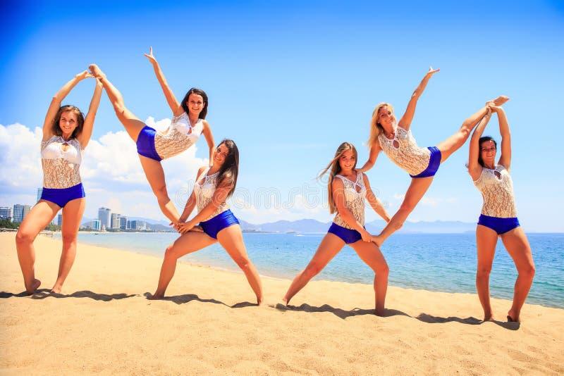 Las animadoras realizan estiramiento doble del talón en la arena contra el mar fotos de archivo libres de regalías