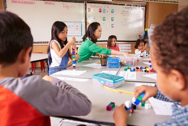 Las aplicaciones elementales del profesor de escuela bloquean el juego en clase con los niños foto de archivo libre de regalías