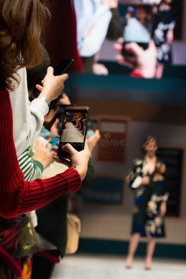 Las audiencias utilizan smartphone que el teléfono móvil toma la foto foto de archivo libre de regalías
