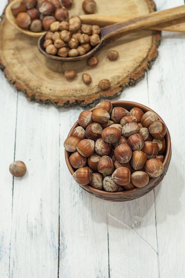 Las avellanas en cáscara en arcilla marrón ruedan en un backgrou de madera blanco imagen de archivo libre de regalías